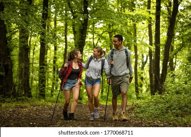 Group of young people hiking trough forest.Outdoors nature concept.