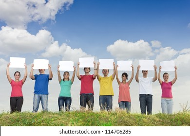 Group of young people holding blank papers in nature
