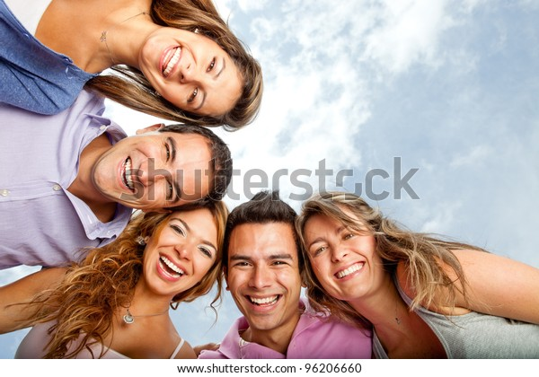 Group of young people hugging and laughing