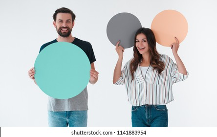 Group of young people isolated on white background. Attractive youth standing together with empty circle advertisement boards.