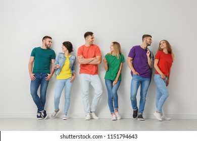 Group of young people in jeans and colorful t-shirts near light wall