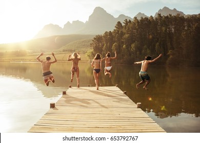 Group of young people jumping into the water from a jetty. Group of friends jumping from pier in the lake on a sunny day.