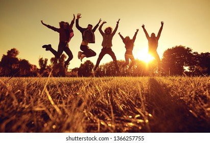 A group of young people jumping on the grass in the park at sunset.