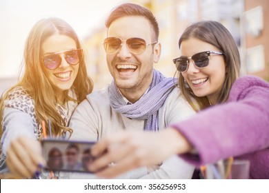 Group of young people laughing and doing a selfie in cafe.It is a nice day with sunshine.