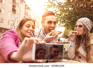 Group of young people laughing and doing a selfie in cafe.They are eating pizza and having a great time. It is a nice day with sunshine.Selective focus