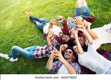 Group of young people laying on the grass in circle, using phones