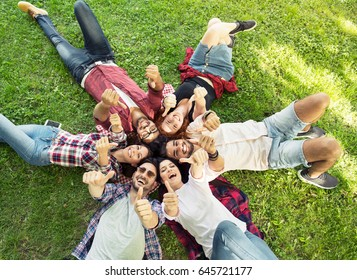 Group of young people laying on the grass in circle, thumbs up, happy