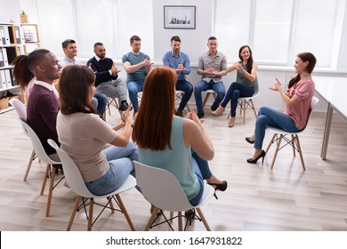 Group Of Young People Learning Deaf Gesture Sign From Woman Sitting On Chair