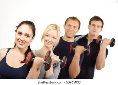 Group of young people lifting weights in the gym