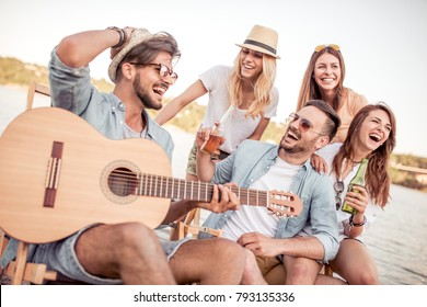 Group of young people listening to friend,playing guitar outdoors.Young friends drinking beers and enjoying music.