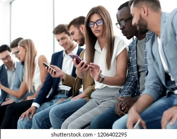 group of young people looking at the screens of their smartphones