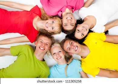group of young people lying down on floor in circle, teenage students happy smile top angle view over white background