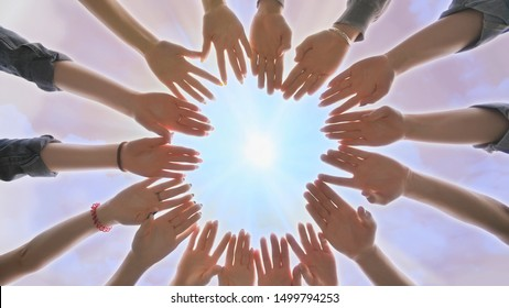 A group of young people make a circle out of their hands. Diverse People Hands Together Partnership.