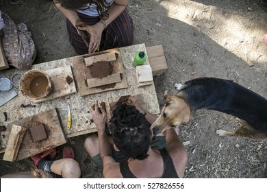 A group of young people making terra cotta with his dog.