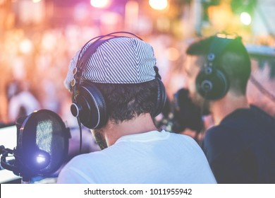 Group of young people making a video feed from night party outdoor - Friends vloggers recording a live streaming at music festival event - New technology trends concept - Focus on left headphones
