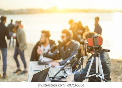 Group of young people making a video feed from beach party at sunset - Man vlogger using mobile phone camera for filming festival event - New technology trends concept - Focus on smartphone
