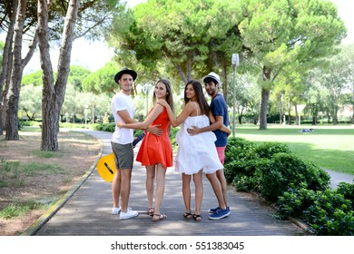 group of young people man and woman walking together on a sidewalk in a vacation beach resort park during sunny summer holiday