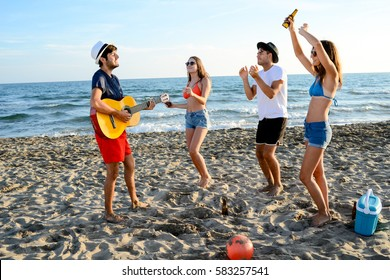 group of young people man and woman with guitar dancing and having fun and party on the beach at summer sunset holiday vacation