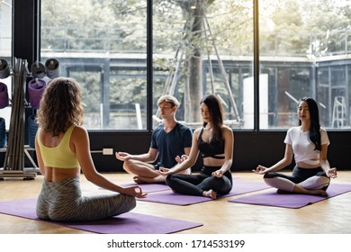 Group of young people meditate yoga on yoga mat, with an exemplary trainer in exercise room. Young women, man and their teacher practicing yoga in gym. Concept of exercise with yoga.