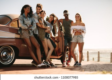 Group of young people on road trip standing by the car. Diverse group of friends on a summer road trip.