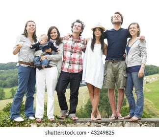 Group of young people, with one woman holding a baby, standing on a stone wall outdoors. Horizontal.