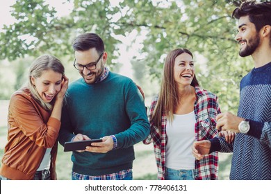 Group of young people in park with digital tablet having fun