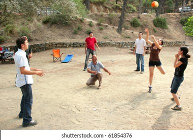 Group of young people playing ball in the forest.