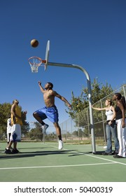 Group of young people playing basketball, one player jumping for ball