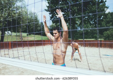 Group of young people playing beach volleyball on beautiful sunny day.