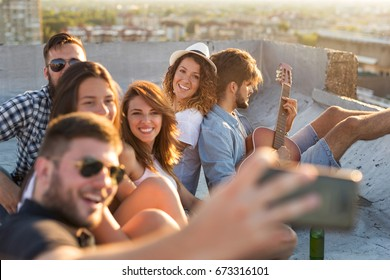 Group of young people playing the guitar, singing and having fun at a rooftop party