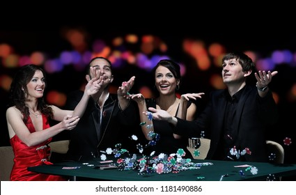 Group of young people playing poker at the gambling house