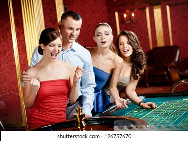 Group of young people playing roulette at the gambling house