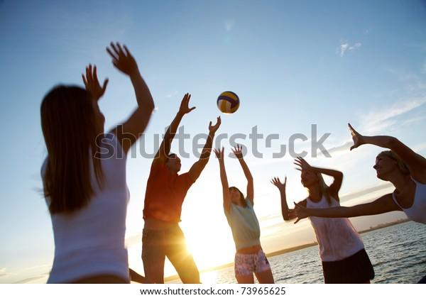 Gruppe junger Leute, die am Strand Volleyball spielen