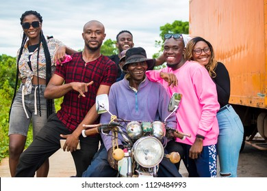 group of young people posing with an elderly man on a motorcycle. group of african people both young and old happy together