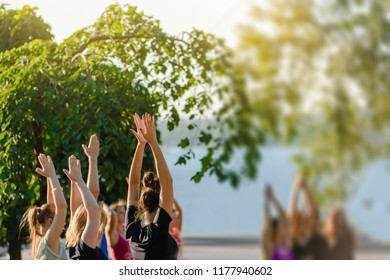 Group of young people practicing yoga outside in park