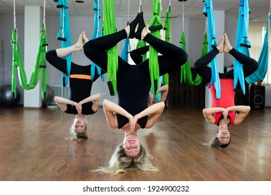 Group of young people practicing yoga on hammock at health club. Fitness, stretch, balance, exercise and healthy lifestyle people