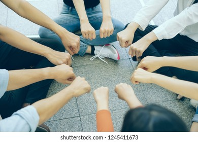 Group of young people putting their fists together in a circle concept on top of the floor.Trust, friendship, unity, cooperation concept.