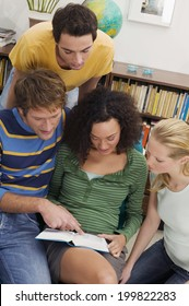Group of young people reading book