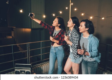 group of young people in rooftop party taking selfie by cellphone smiling. charming girls using mobile phone self portrait on the roof outdoors at night. happy women enjoy music from radio with beers