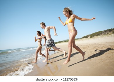 group of young people running into the sea