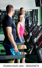 group of young people running on treadmills in sport gym