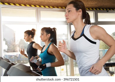 Group of young people running on treadmill in gym.
