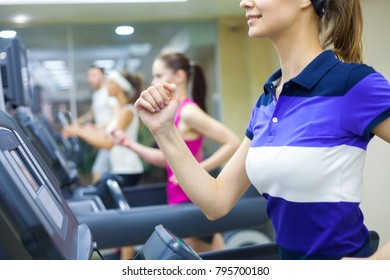 group of young people running on treadmill in gym