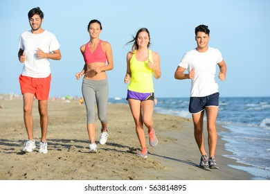 group of young people running in the sand on the shore of a beach by the sea at sunset during a sunny summer holiday vacation
