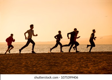 group of young people runs at the beach on beautiful summer sunset