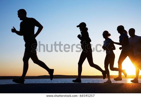 美しい夏の夕日の海岸を若い人たちが走る