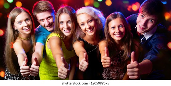 Group of young people show thumb up together at party.