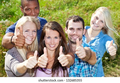 Group of young people showing thumbs up.
