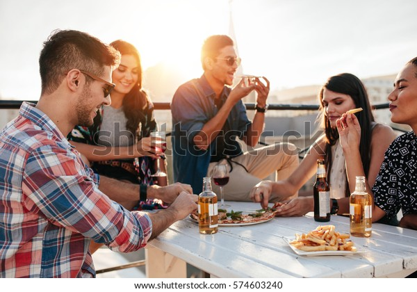 Eine Gruppe junger Leute, die herumsitzen und Pizza essen. Freunde feiern und Pizza essen.