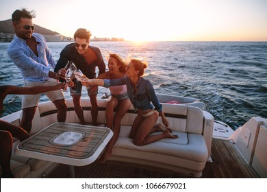 Group of young people sitting at the back of a yacht and toasting drinks. Young people having a boat party at sunset.